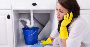 Woman In Front Of Water Leaking From Sink Pipe